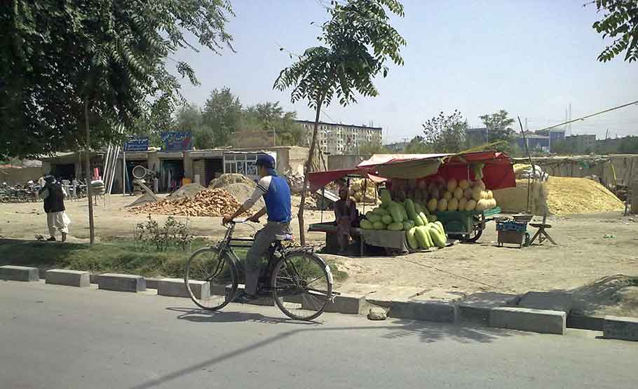 Afghan man bicycling on road