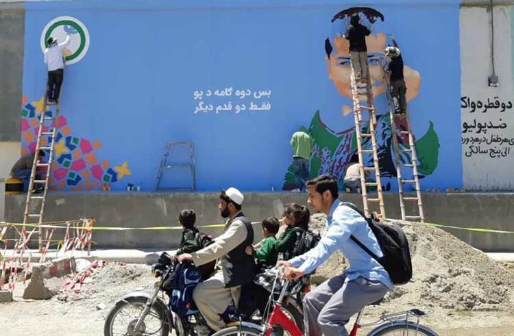 Afghan teens painting wall