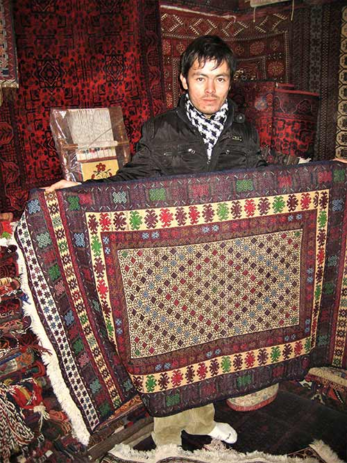 Afghan guy selling rugs