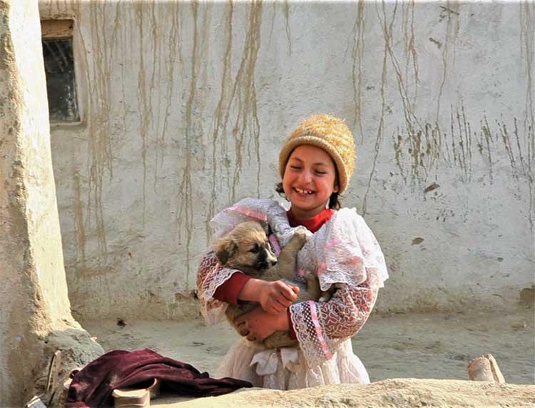 Afghan boy holding puppy