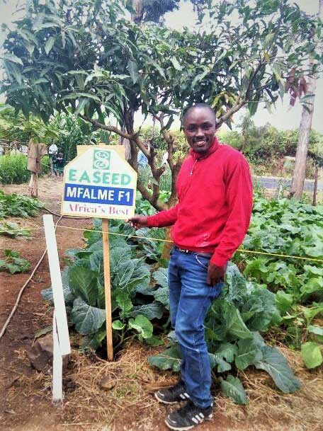 Mwanzia standing next to garden