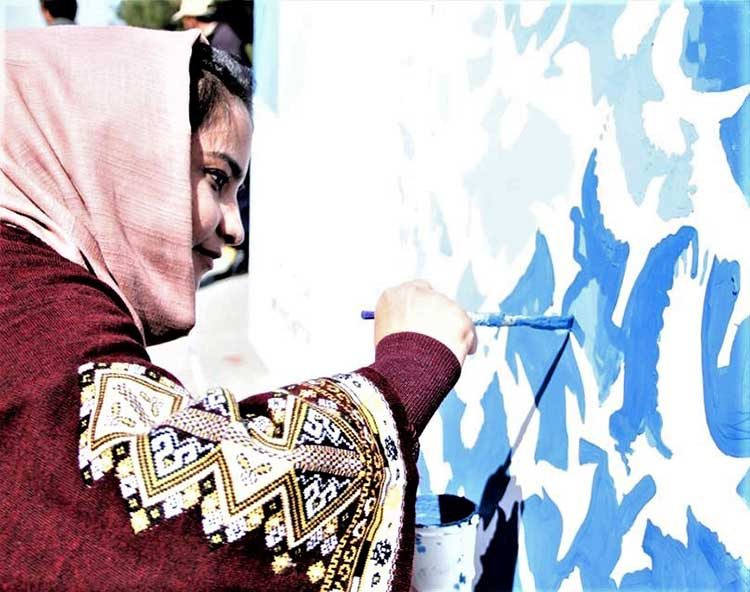 Afghan girl painting wall